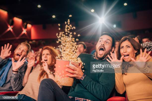 terrified people spilling popcorn - horror movie stock photos and pictures