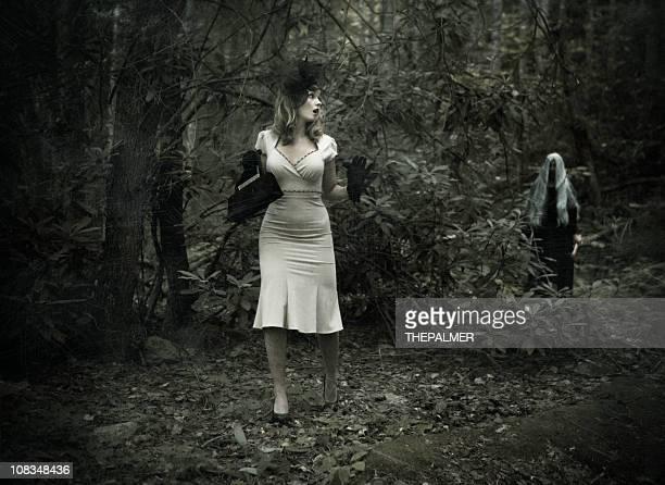 Aterrorizado mujer en el bosque conseguido por una bruja