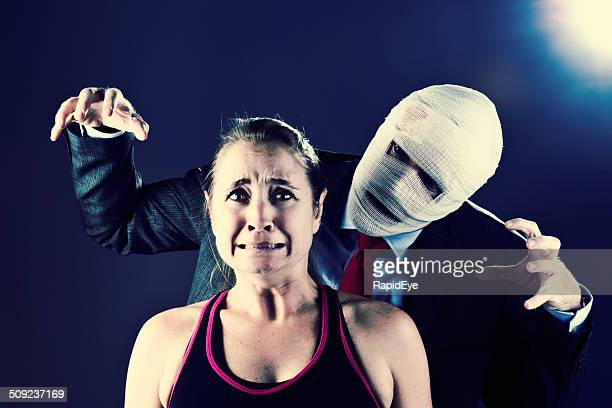 terrified woman menaced by man disguised in bandages: horror movie! - horror movie stock photos and pictures