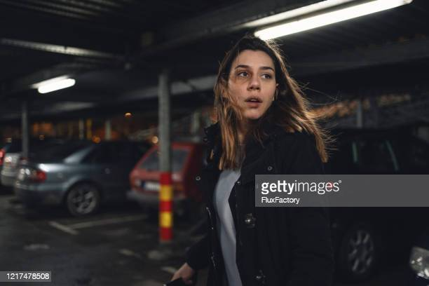 terrified woman walking on a parking lot - victim stock pictures, royalty-free photos & images
