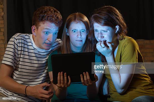 Terrified Young Adults Streaming Scary Movie on Digital Tablet Computer