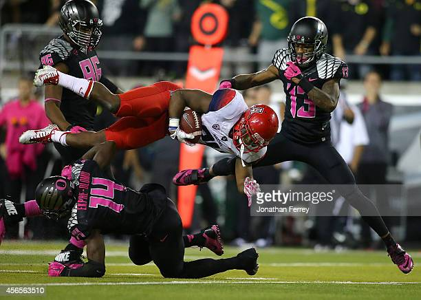 Terris JonesGrisby of the Arizona Wildcats dies through the air against Ifo EkpreOlomu and Troy Hill of the Oregon Ducks at Autzen Stadium on October...