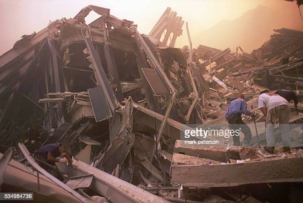 Terrorist attack on the World Trade Center Rescue crews engulfed in a fog of dust set about the task of finding survivors Photo by Mark...