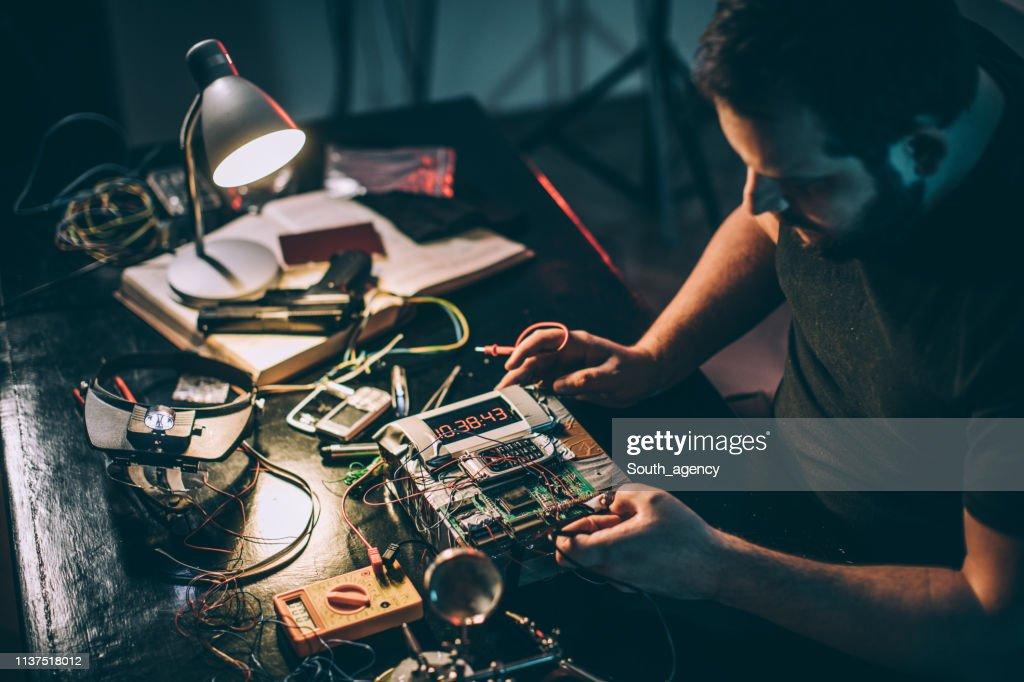 Terrorist in workshop constructing a bomb : Stock Photo