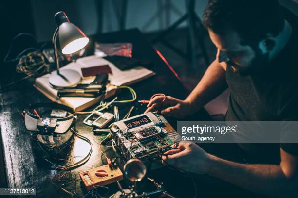 terrorist in workshop constructing a bomb - detonator stock photos and pictures