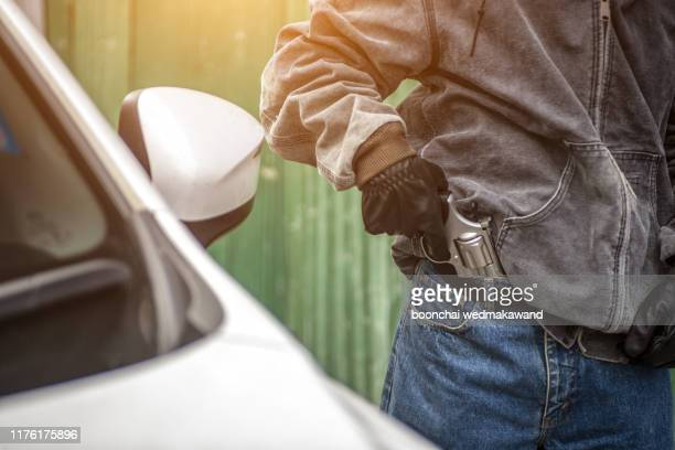 terrorist or a car thief pointing a gun at the driver - car owner - weaponry stock pictures, royalty-free photos & images