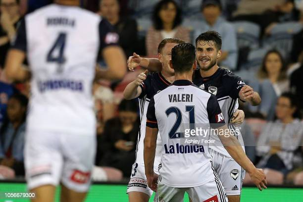 Terry Antonis of Melbourne Victory celebrates his goal with team mates during the round three ALeague match between the Newcastle Jets and the...