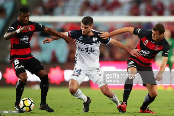 Terry Antonis of the Victory is challenged by Roly Bonevacia and Oriol Riera of the Wanderers during the round 17 ALeague match between the Western...