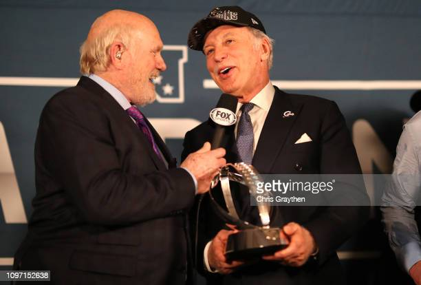 Terry Bradshaw presents Stanley Kroenke owner of the Los Angeles Rams the NFC Championship trophy after defeating the New Orleans Saints in the NFC...