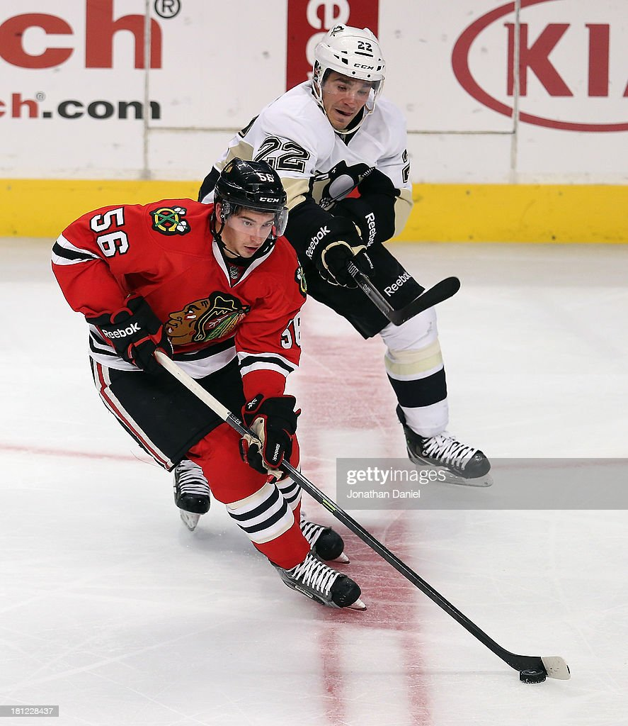 Terry Broadhurst #56 of the Chicago Blackhawks controls the puck under pressure from Matt D'Agostini #22 of the Pittsburgh Penguins during an exhibition game at United Center on September 19, 2013 in Chicago, Illinois. The Penguins defeated the Blackhawks 4-3 in a shootout.