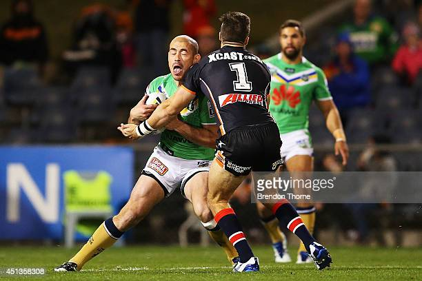 Terry Campese of the Raiders is tackled by James Tedesco of the Tigers during the round 16 NRL match between the Wests Tigers and the Canberra...