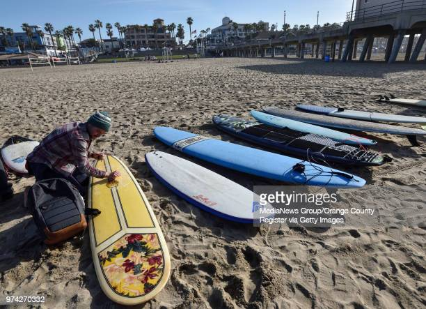Terry Diamond waxes his surfboard before joining more than 100 surfers during a paddle out to honor Pierre Agnes CEO of Quiksilver in Huntington...
