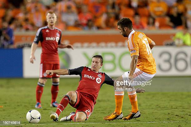Terry Dunfield of Toronto FC slides in front of Will Bruin of the Houston Dynamo for the ball at BBVA Compass Stadium on August 25 2012 in Houston...