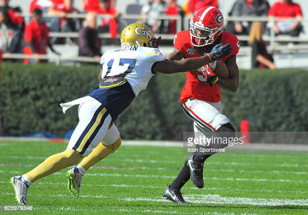 Terry Godwin Georgia Bulldogs wide receiver stiff arms Lance Austin Georgia Tech Yellow Jackets defensive back as he carries the ball after a...