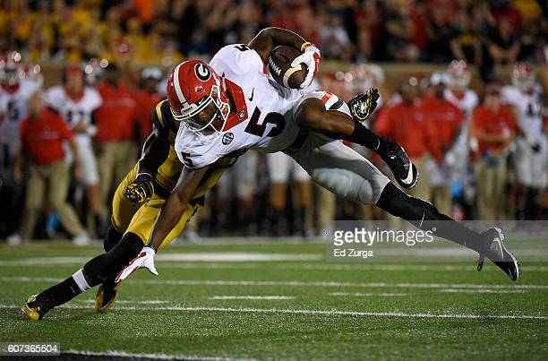 Terry Godwin of the Georgia Bulldogs is stopped short of the end zone by Aarion Penton of the Missouri Tigers in the second quarter at Memorial...