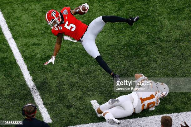 Terry Godwin of the Georgia Bulldogs is tackled by Brandon Jones of the Texas Longhorns during the first half of the Allstate Sugar Bowl at the...