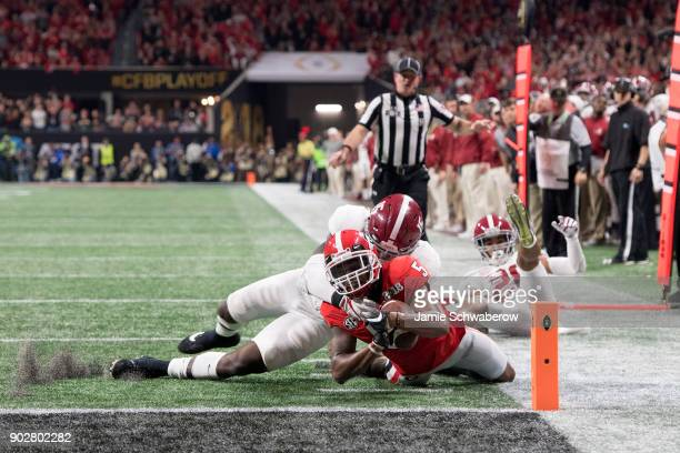 Terry Godwin of the Georgia Bulldogs is tackled near the goal line against Ronnie Harrison of the Alabama Crimson Tide during the College Football...