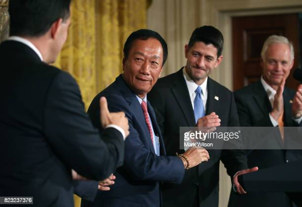 Terry Gou chairman of Apple supplier Foxconn shakes hands with Wisconsin Gov Scott Walker as House Speaker Paul Ryan looks on at news conference held...