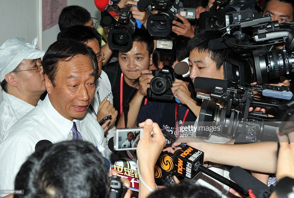 Terry Gou (L), chairman of Foxconn's Taiwanese parent company Hon Hai Precision, is surrounded by journalists as he arrives for an open visit of the Foxconn plant in Shenzen on May 26, 2010. The Taiwanese boss of Apple manufacturer Foxconn headed to a sprawling factory in southern China where a spate of worker suicides have stoked anger about labour conditions. Gou, the chairman of Foxconn's parent company Hon Hai Precision, flew into the booming city of Shenzhen aboard his private jet with travelling Taiwanese reporters, urging the media to see the factory for themselves.
