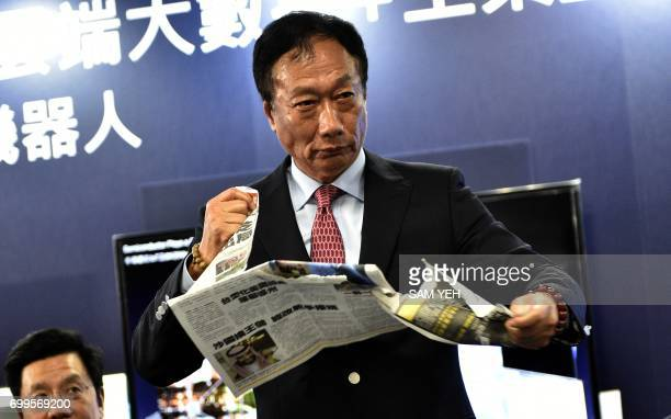 Terry Gou Chairman of Taiwan's Foxconn also known as Hon Hai tears apart a Chinese version of the Commercial Times during a press conference in New...