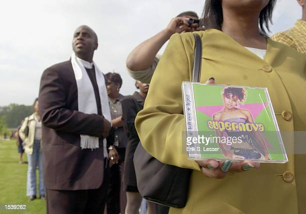 Terry Holmes of Florida holds a CD by Lisa Left Eye Lopes while waiting in line to attend the public funeral of the TLC singer at the New Birth...