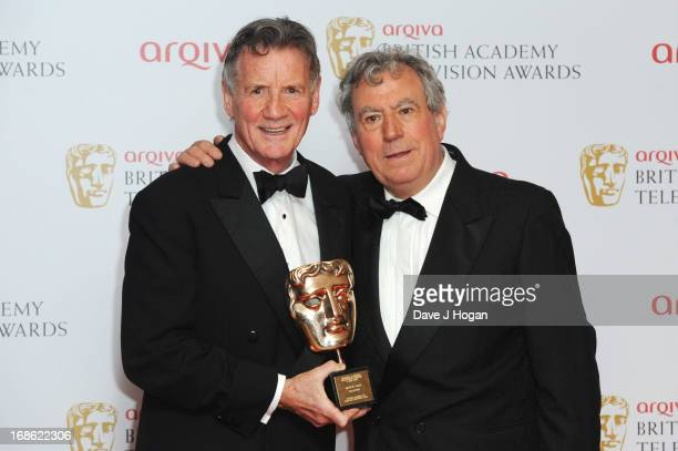Terry Jones poses with Michael Palin after presenting him with The Fellowship Award in front of the winners boards at the BAFTA TV Awards 2013 at The...