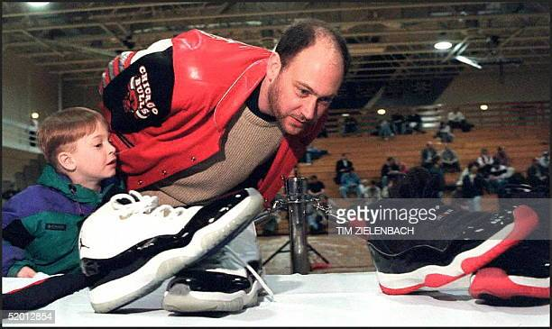 Terry Keigher and Steve Ryan look at autographed shoes worn by Chicago Bulls guard Michael Jordan in the 1996 playoffs at an auction of Bulls...