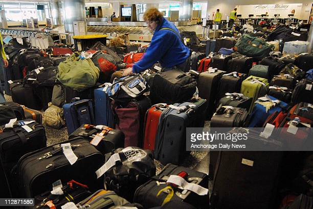 Terry Lamberson searches for her luggage at Ted Stevens Anchorage International Airport in Alaska on March 31 amongst hundreds of bags being held...
