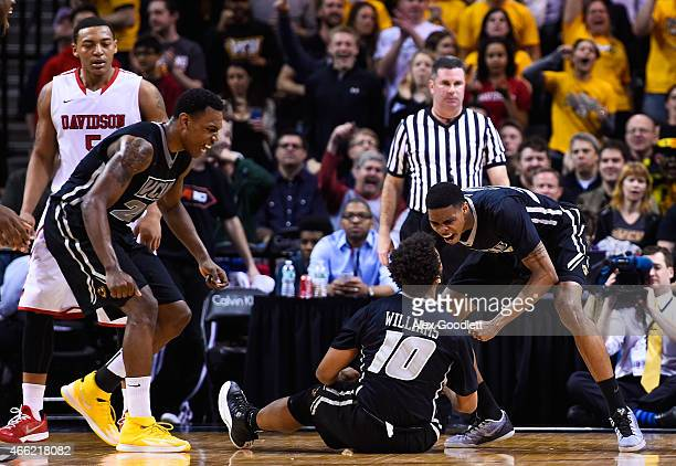 Terry Larrier celebrates a foul with Jonathan Williams of the Virginia Commonwealth Rams during a semifinal game against the Davidson Wildcats in the...