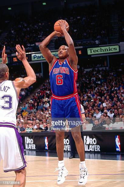 Terry Mills of the Detroit Pistons shoots against Brian Grant of the Sacramento Kings during a game played on February 26 1996 at Arco Arena in...