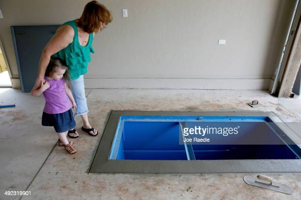 Terry Moore shows her granddaughter, Jayzlei Blackwell the newly installed Storm Safe Shelter tornado shelter in the floor of the garage almost one...