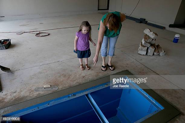 Terry Moore shows her granddaughter Jayzlei Blackwell the newly installed Storm Safe Shelter tornado shelter in the floor of the garage almost one...