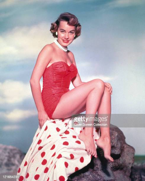 Terry Moore US actress wearing a red swimsuit and white necklace as she poses on a white towel with red polka dots which as been placed over a rock...
