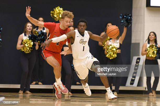 Terry Nolan Jr #1 of the George Washington Colonials dribbles around Miles Latimer of the Stony Brook Seawolves during a college basketball game at...