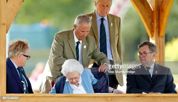 Terry Pendry helps Queen Elizabeth II put on her gilet as she watches her horse 'Sparkler' compete in the Flat Ridden Sport Horse class on day 1 of...