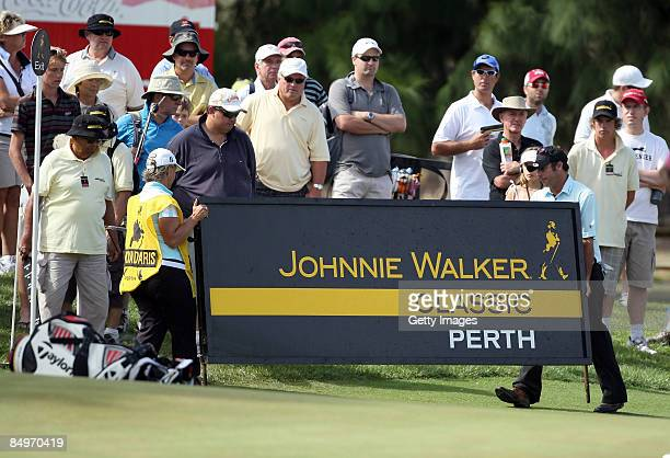 Terry Pilkadaris of Australia and his wife Monique who was caddying for him move a advertising board at the 4th hole during the final round of the...