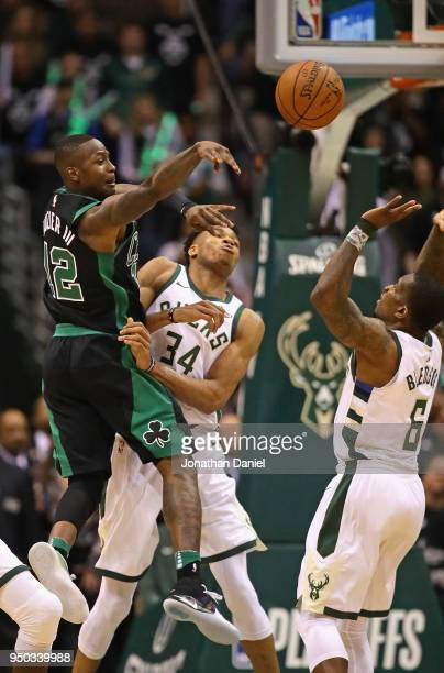 Terry Rozier of the Boston Celtics leaps to pass over Giannis Antetokounmpo and Eric Bledsoe of the Milwaukee Bucks during Game Four of Round One of...