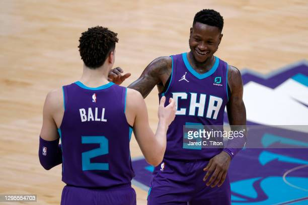 Terry Rozier of the Charlotte Hornets celebrates with teammate LaMelo Ball following their victory over the Atlanta Hawks at Spectrum Center on...