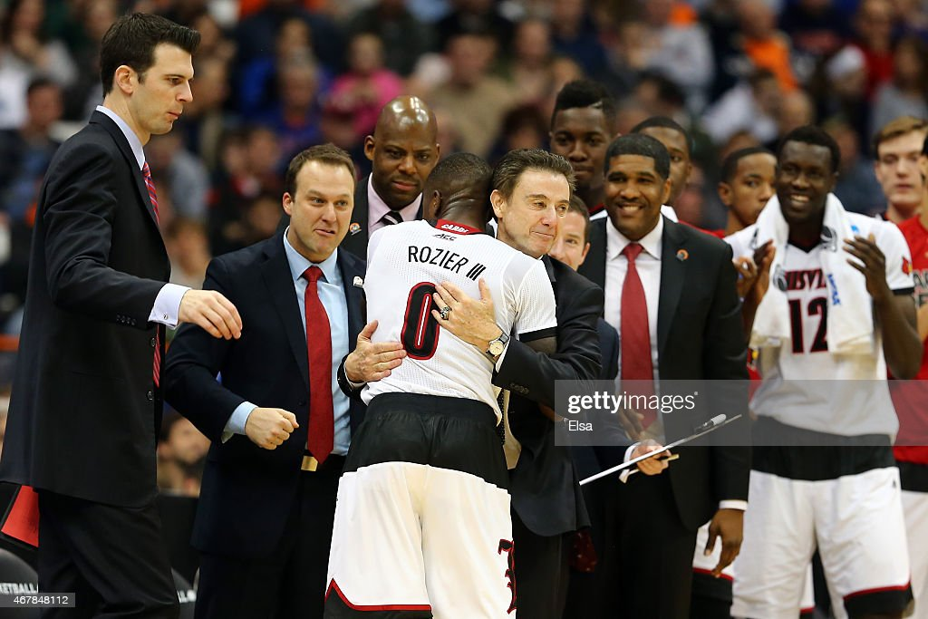 Terry Rozier #0 of the Louisville Cardinals celebrates with head coach Rick Pitino after defeating the North Carolina State Wolfpack 75 to 65 during the East Regional Semifinal of the 2015 NCAA Men's Basketball Tournament at the Carrier Dome on March 27, 2015 in Syracuse, New York.