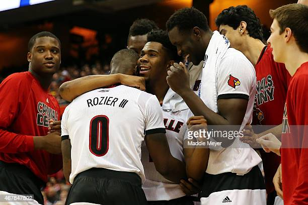 Terry Rozier of the Louisville Cardinals celebrates with his teammates Anton Gill and Mangok Mathiang after defeating the North Carolina State...
