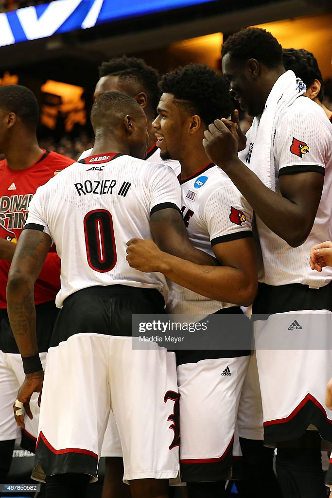 Terry Rozier #0 of the Louisville Cardinals celebrates with his teammates Anton Gill #1 and Mangok Mathiang #12 after defeating the North Carolina State Wolfpack 75 to 65 during the East Regional Semifinal of the 2015 NCAA Men's Basketball Tournament at the Carrier Dome on March 27, 2015 in Syracuse, New York.