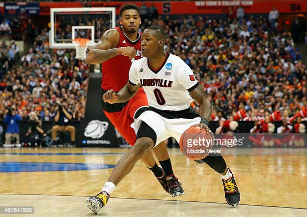 Terry Rozier of the Louisville Cardinals dribbles against Trevor Lacey of the North Carolina State Wolfpack in the second half of the game during the...