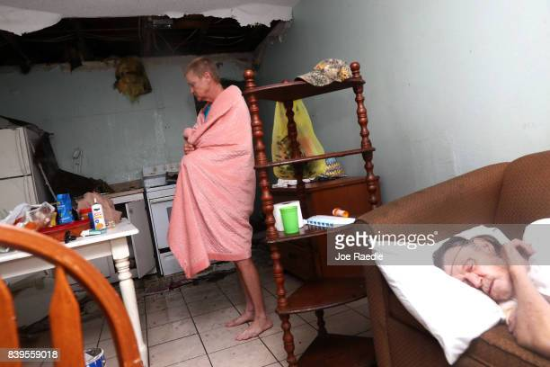 Terry Smith stands in the kitchen as Henry McKay sleeps in the apartment where the ceiling collapse when Hurricane Harvey hit on August 26 2017 in...