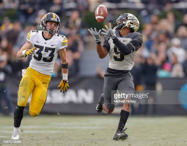 Terry Wright of the Purdue Boilermakers catches a pass and would go on to score a touchdown as Riley Moss of the Iowa Hawkeyes pursues at RossAde...
