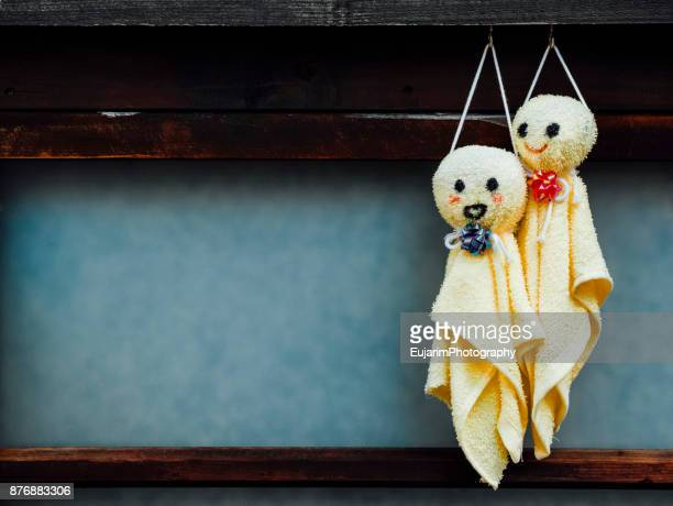 Teru teru bozu dolls made of yellow hand towels hanging on the window