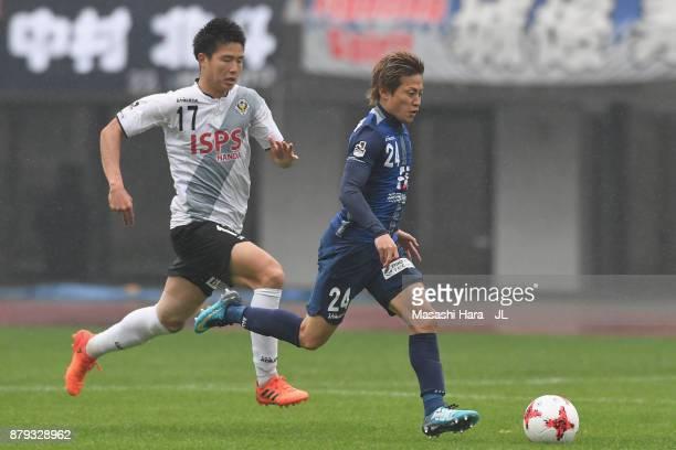 Teruhito Nakagawa of Avispa Fukuoka and Tatsuya Uchida of Tokyo Verdy compete for the ball during the JLeague J1 Promotion PlayOff semi final match...