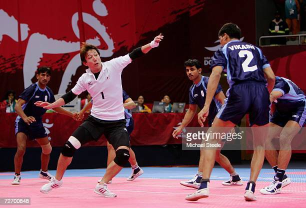 Terukazu Nitta of Japan makes a raid on the Indian team during the Men's Kabaddi Round Robin match between Japan and India at the 15th Asian Games...
