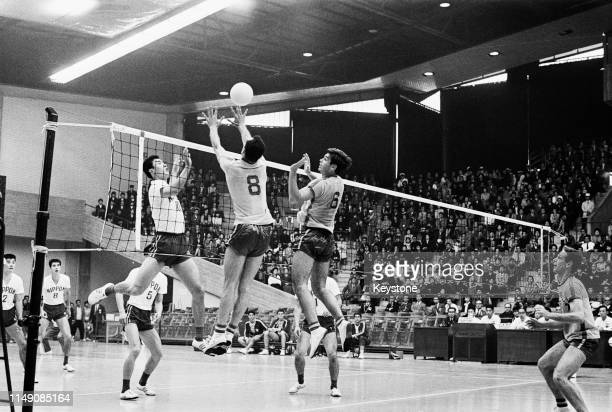 Terushia Moriyama of Japan attempts to spike the ball but is blocked by Ramalho Oliveira and Marco Antonio Volpi of Brazil during the Men's Olympic...