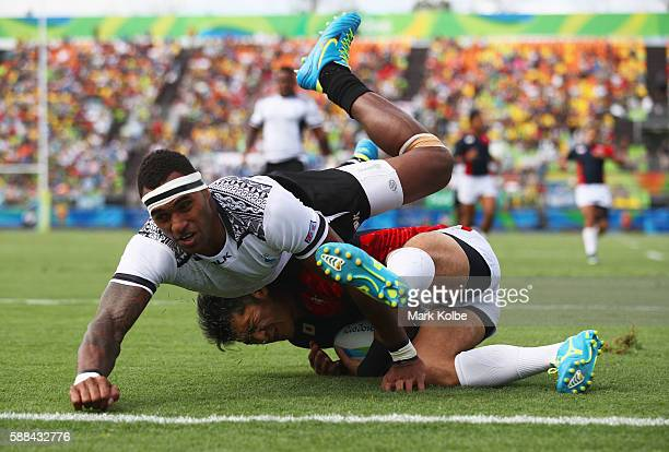 Teruya Goto of Japan scores a try under pressure from Semi Kunatani of Fiji score a try during the Men's Rugby Sevens semi final match between Fiji...
