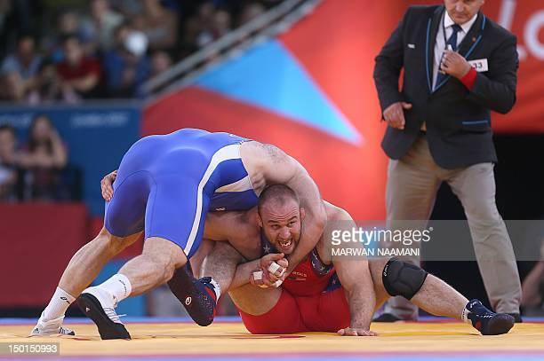 US' Tervel Ivaylov Dlagnev wrestles Uzbekistan's Artur Taymazov in their Men's 120kg Freestyle semifinal match on August 11 2012 during the wrestling...